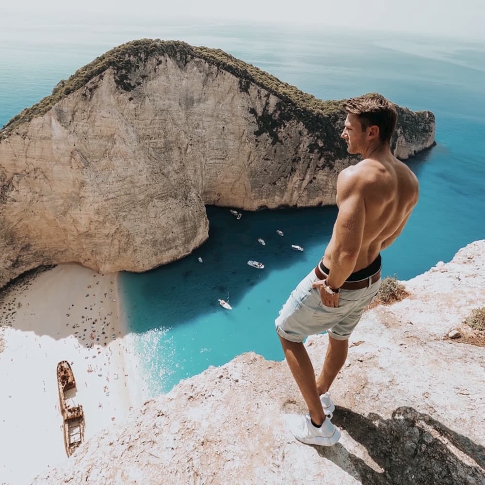 Remove objects from a photo, clone stamp, a man standing on a cliff, a man and the sea