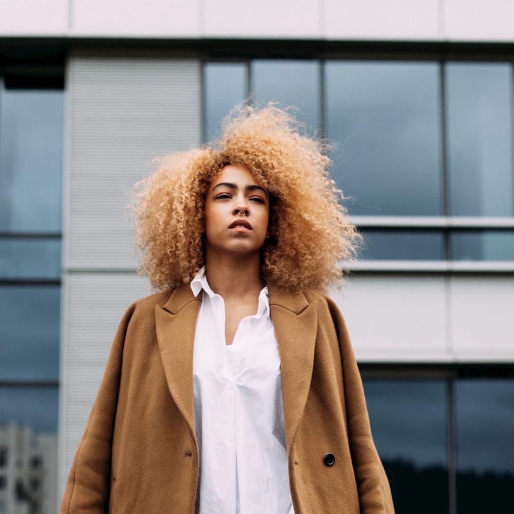 Hair cutout, cutting the hair of a curly girl, a blonde African-American girl